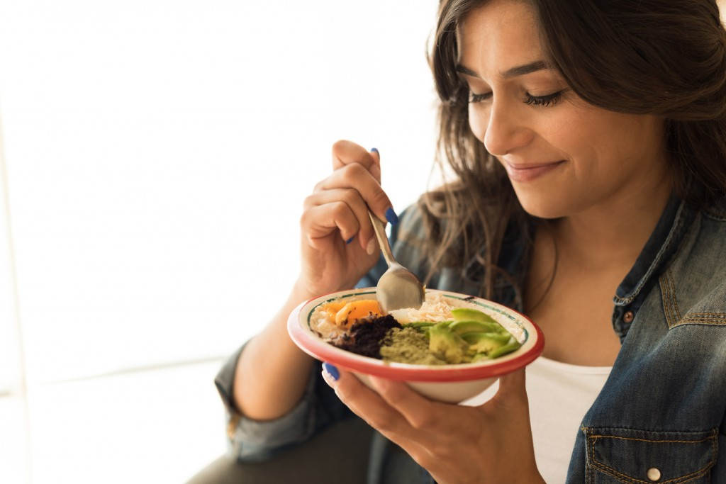 Woman eating a vegan bowl of superfoods